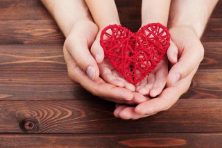 parents and kids with their hands together holding a stylized heart
