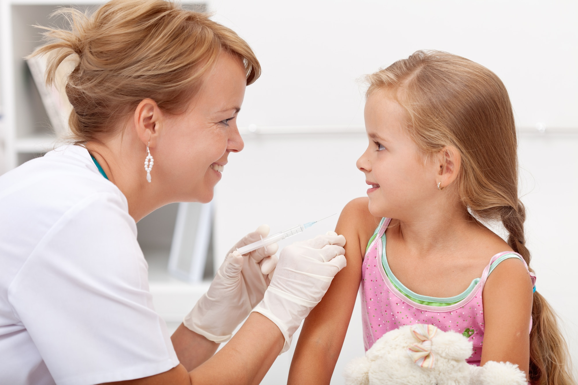 a brave young girl is preparing to receive the flu vaccine injection in her upper arm from a nurse