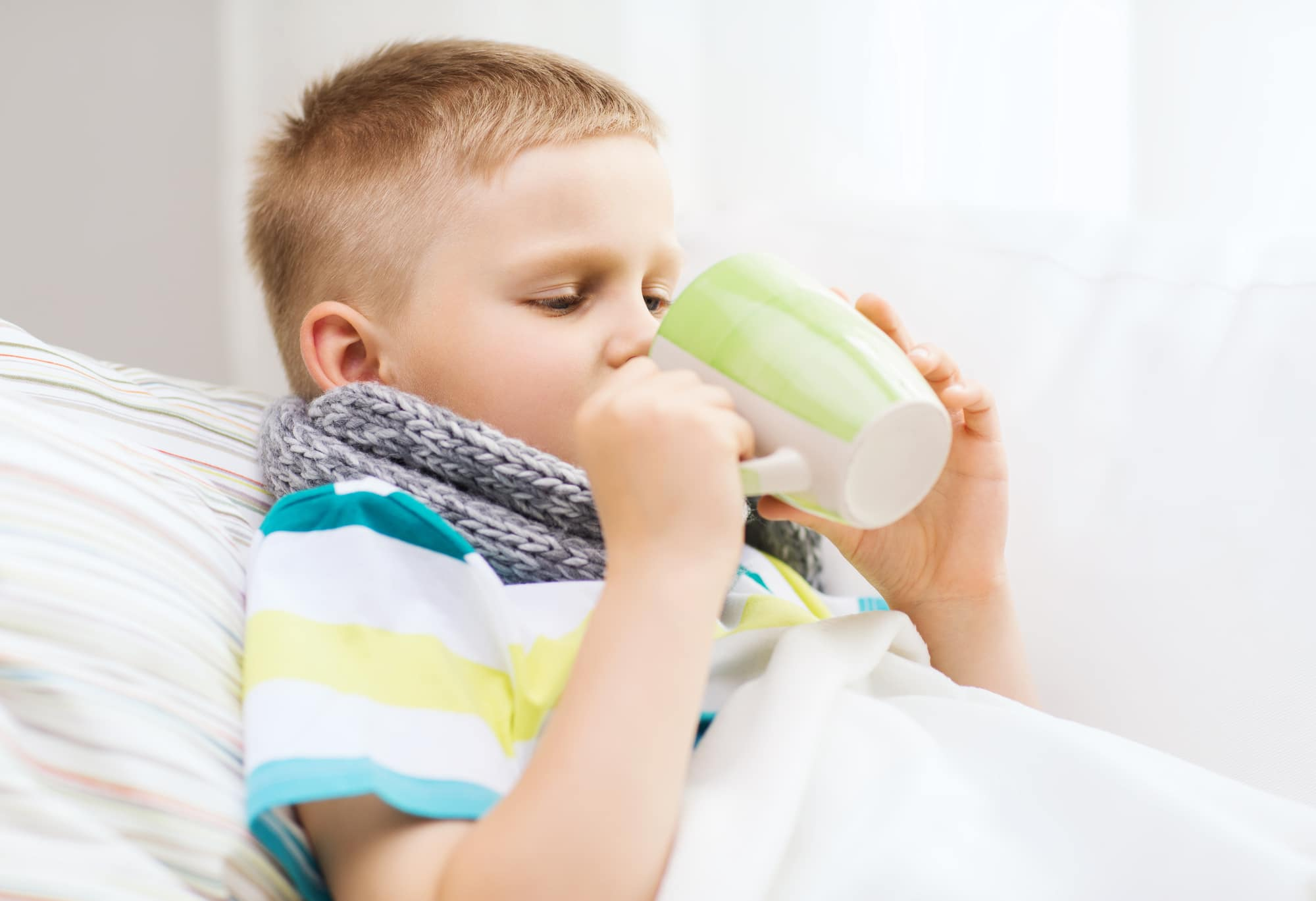 A young boy home with the flu, drinking hot fluids and bundled up to stay warm