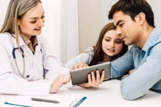 A doctor consulting a father and his daughter who needs focused care for their ADHD/ADD needs